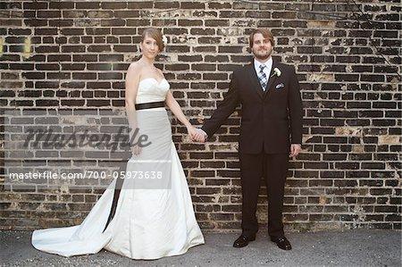 Bride and Groom debout devant le mur de briques