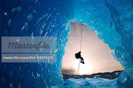 COMPOSITE : Vue depuis l'intérieur d'une grotte de glace d'iceberg congelé comme un grimpeur de glace du lac Mendenhall rappels descendre une corde, Juneau, sud-est de l'Alaska, hiver