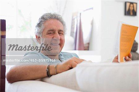 Ein fröhlich Alter Mann zu Hause ein Buch zu lesen