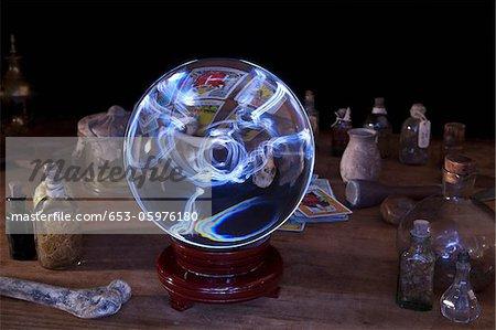 Une boule de cristal au milieu de vieux-mode bouteilles et de cartes de tarot