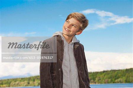 Portrait d'un garçon regardant loin et souriant malicieusement