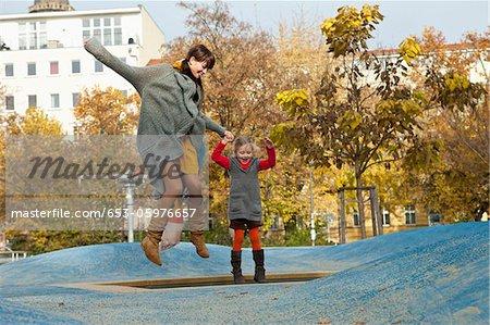 Mère et fille sur petit trampoline dans le parc