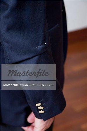 Détail d'une épingle dans la manche de la veste de costume de l'homme