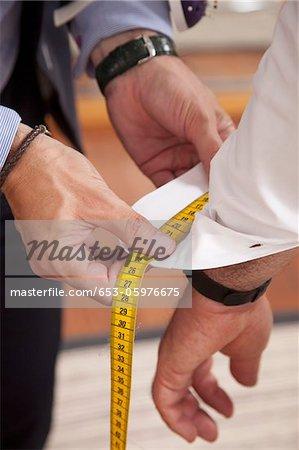 Détail d'un tailleur mesurant la manchette de chemise d'homme
