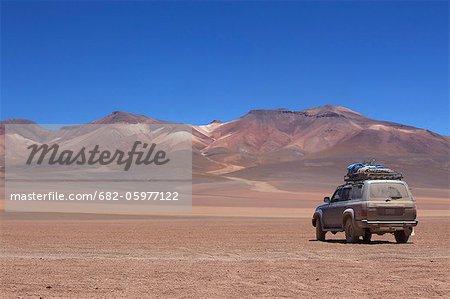 All terrain vehicle in ochre landscape near Las Rocas de Dali, Los Lipez, Southwestern Bolivia, South America.