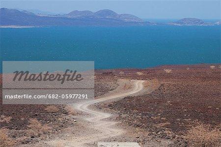 Dirt track leading through volcanic rocks to Lake Turkana- Jade Sea, Loyongalani region, Lake Turkana, Kenya, Africa