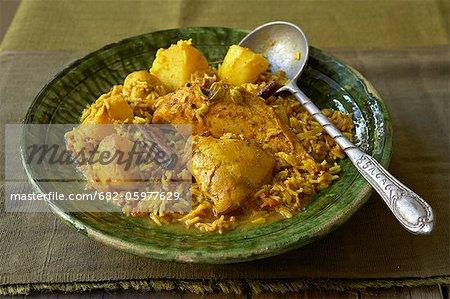 Traditional African cooking. Chicken breyani. Ingredients: chicken pieces, lentils, rice, turmeric, cinnamon, cardamom, potatoes