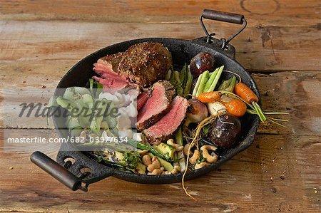 Traditionelle Afrikanisch kochen. Gewürzte Rinderfilet, serviert mit verschiedene Gemüse