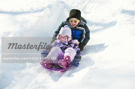 Geschwister ihre Schlitten-Fahrt genießen.