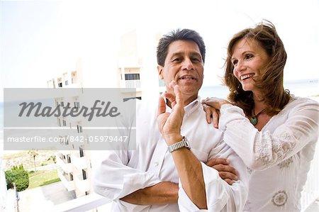 Debout de couple d'âge mûr sur le balcon de condo en bord de mer