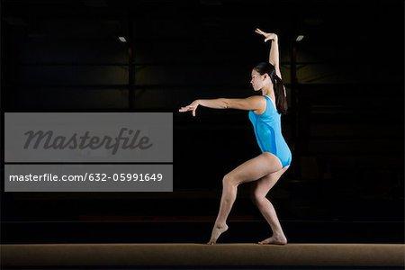 Teenage girl gymnast performing on balance beam