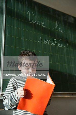 Garçon lire devant le tableau noir dans la salle de classe