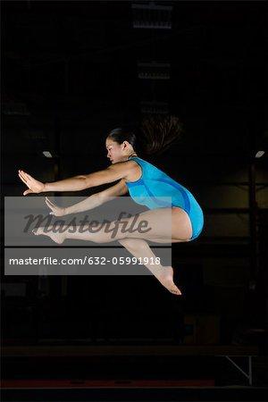 Teenage girl gymnast jumping in air