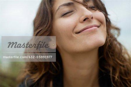 Sourire de jeune fille avec les yeux fermés