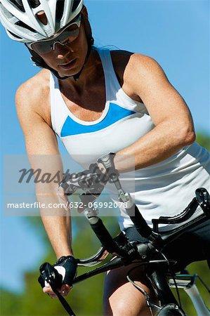 Cycliste féminine contrôle fréquence cardiaque sur la montre bracelet