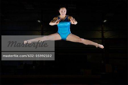 Teenage girl gymnast performing split leap