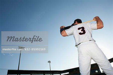 Baseball player holding bat, rear view