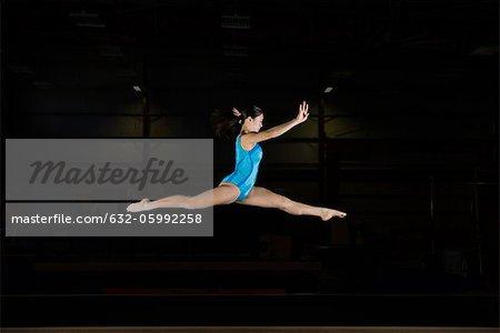 Tenage girl gymnast performing split leap