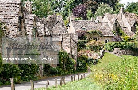 Célèbre ligne Arlington des cottages en pierre du XVIIe siècle avec pente raide toits, Bibury, Cotswolds, Gloucestershire, Royaume-Uni