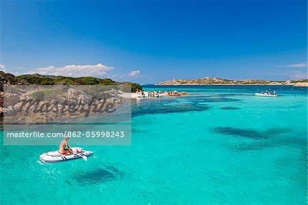 Italie, Sardaigne, Olbia-Tempo, archipel de La Maddalena. Une femme est assise sur un bateau à côté de l'île Budelli.