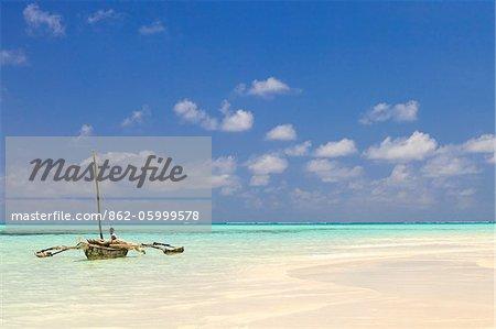 Tanzanie, Zanzibar, Unguja, Jambiani. Un homme est assis sur son bateau.