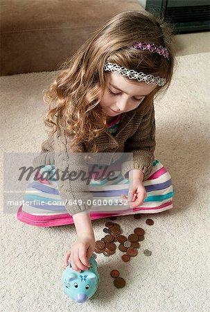 Mädchen setzen Münzen im Sparschwein