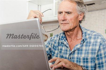 Vieil homme utilisant un ordinateur portable dans la cuisine