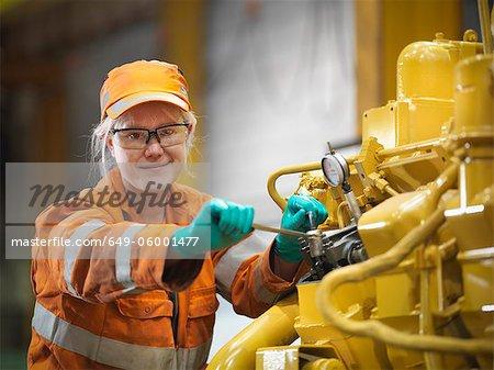 Apprentice engineer at work in factory