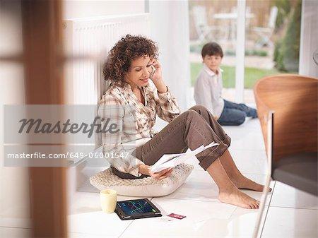 Femme sur téléphone cellulaire contre le radiateur