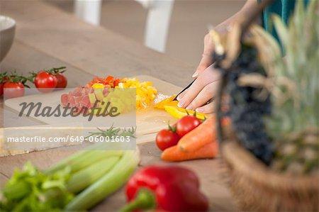 Gros plan de femme hacher les poivrons