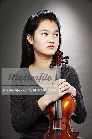 Portrait d'une jeune adolescente asiatique tenant violon