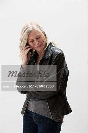 Femme mature, souriant et à l'aide de téléphone portable, studio shot