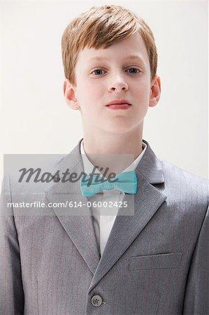 Boy wearing grey suit and bow tie, studio shot