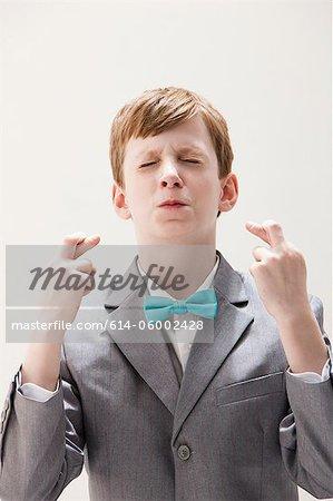 Boy wearing grey suit with fingers crossed, studio shot