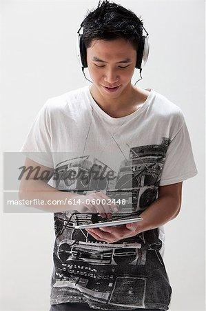Jeune homme asiatique avec un casque, à l'aide de la tablette numérique studio shot