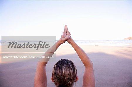 Nahaufnahme von den Händen der Frau im Baum-Yoga-Pose am Strand