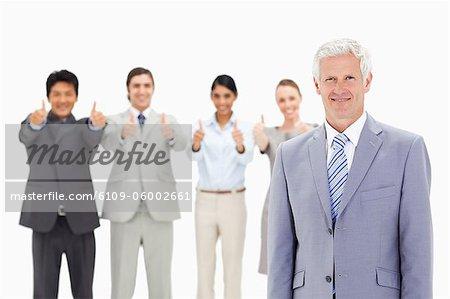 Gros plan d'une équipe multiculturelle d'affaires avec leur pouce vers le haut avec un homme mûr au premier plan