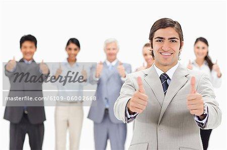 Gros plan d'une équipe multiculturelle d'affaires avec leur accent pouce vers le haut sur un homme souriant au premier plan