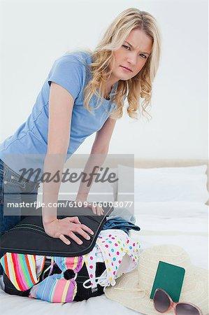 Un plan d'une femme agacée essayant de fermer sa valise sur le lit en appuyant dessus rapproché.