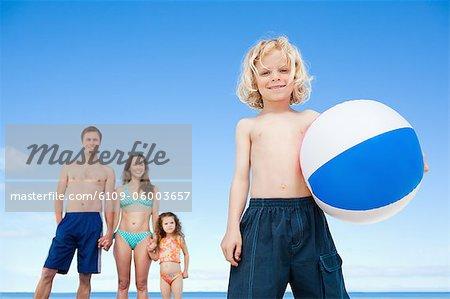 Jeune garçon avec un ballon de plage et de sa famille derrière lui sur la plage
