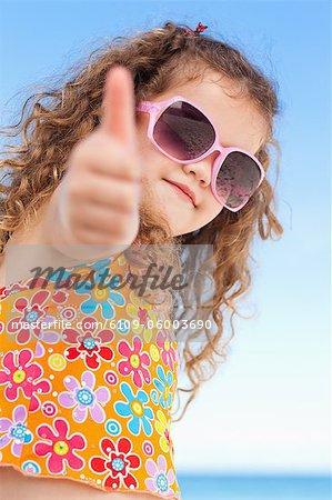 Adorable petite fille sur la plage donnant le pouce vers le haut