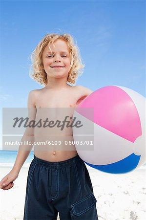 Petit garçon sur la plage avec ballon de plage