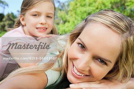 Une vue de côté d'un sourire mère et fille couché sur l'herbe dans le parc