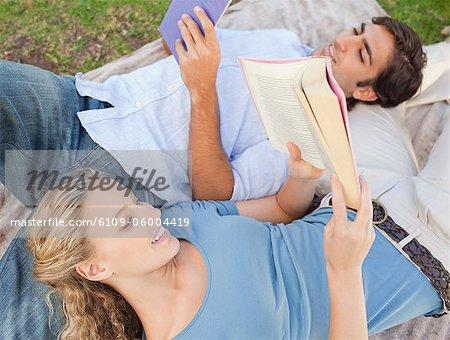 Junges Paar beim Lesen ihrer Bücher auf dem Rasen liegend lächelnd