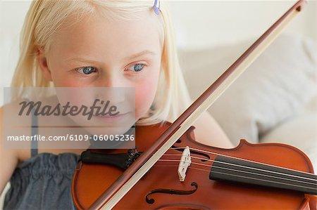 Eine Mädchen lächelt als She Praktiken auf der Geige
