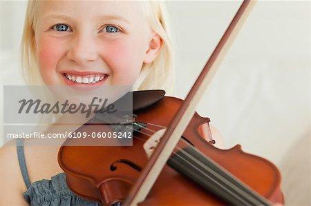 Ein Mädchen mit einem Lächeln die Violine beim Spielen