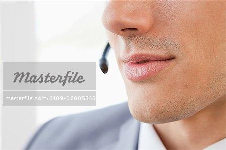 Nahaufnahme eines Mannes Mund reden mit einem Headset in einem hellen Büro