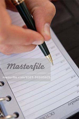 Close-up auf einen Organizer, wo ein Mann schreibt