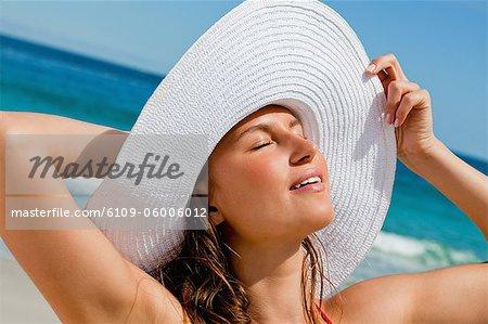 Jeune femme séduisante, bronzer tout debout sur la plage