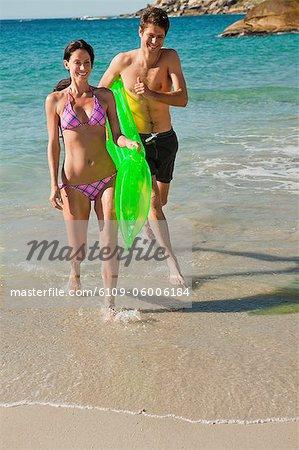 Couple court de la mer avec un matelas d'air avec l'océan en arrière-plan